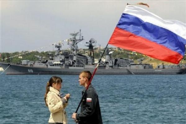 A supporter of Russia with part of the Black Sea Fleet behind him in Sevastopol.